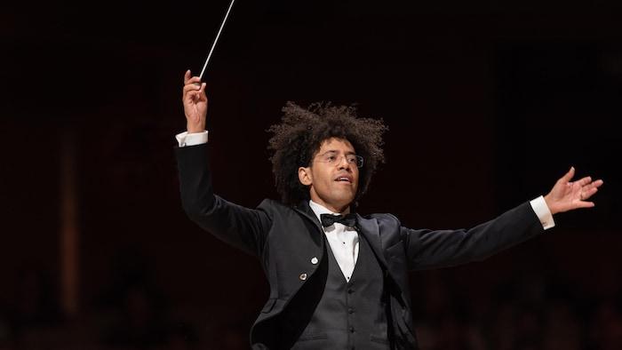 Le chef dirige l'orchestre, baguette en l'air.