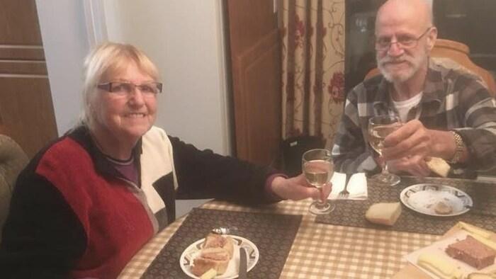 Un verre de vin à la main, du pâté sur la table