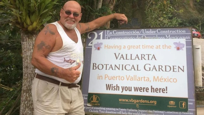 A man stands next to a promotional billboard in Puerto Vallarta, Mexico.