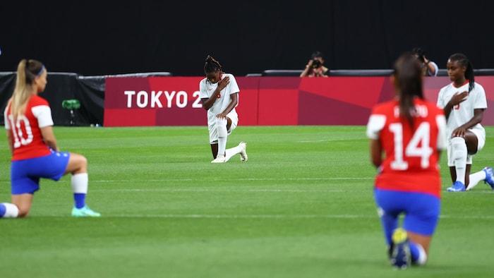 Quatre joueuses de soccer, deux du Chili et deux du Canada, ont un genou au sol sur un terrain de soccer.