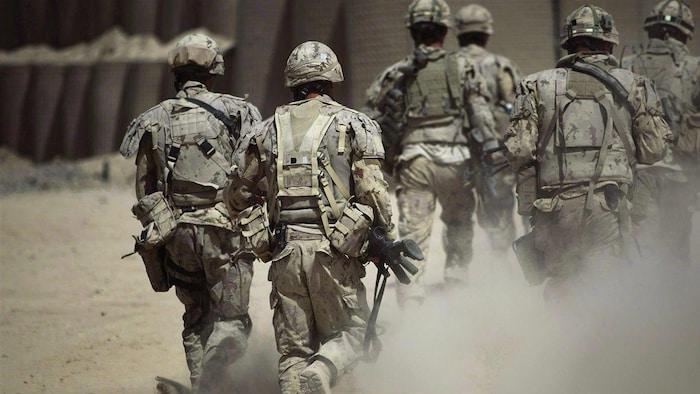 جنود بثياب مموّهة يظهرون من الخلف.