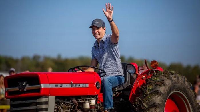Justin Trudeau conduce un tractor en una feria rural.