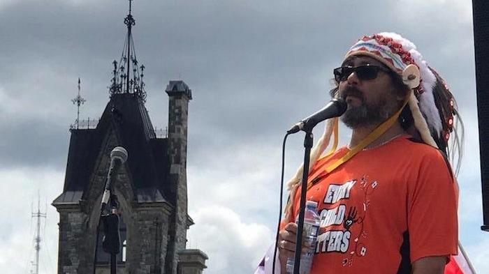 El jefe indígena Tony Wawatie, de la comunidad algonquina de Lac-Rapid habla ante el micrófono frente al Parlamento de Canadá.