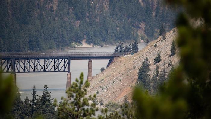 Un pont ferroviaire enjambe le fleuve Fraser alors qu'un feu de forêt brûle à Lytton, en Colombie-Britannique.
