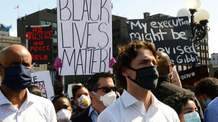Un manifestante sostiene un cartel de Black Lives Matter detrás del primer ministro Justin Trudeau.