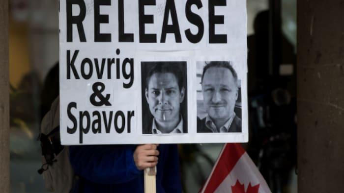"""孟晚舟引渡案审理期间,抗议者手拿""""释放两名麦克""""的牌子在BC省最高法院门前抗议。"""