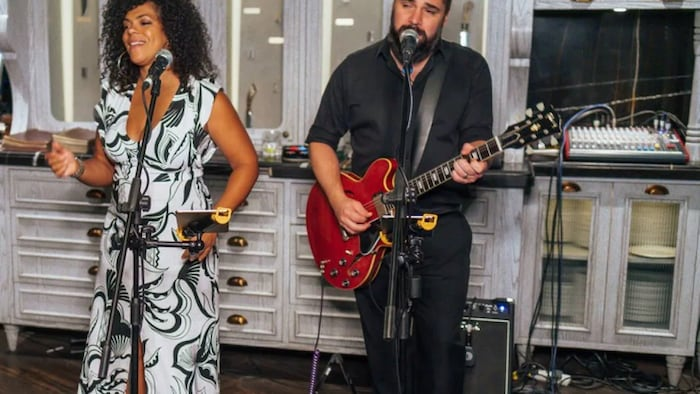 Janelle Thomas, 43, is a singer originally from Victoriaville, Que., who now works in UAE. She says Ottawa's approach of excluding vaccines that haven't been approved in Canada is alienating Canadians overseas. In this photo, Thomas and her husband Félix perform at the Weslodge Saloon in Dubai.
