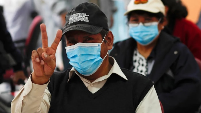 A man flashes a victory sign after getting a shot of the Sputnik V vaccine for COVID-19 at the start of vaccinations for people over age 60 at the Universidad Mayor de San Andres public university in La Paz, Bolivia, Tuesday, April 27, 2021.