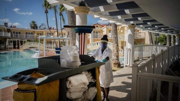 Wearing a mask against the spread of the new coronavirus, a maid goes to clean the rooms at the Hotel Comodoro in Havana, Cuba, Thursday, Feb. 11, 2021.