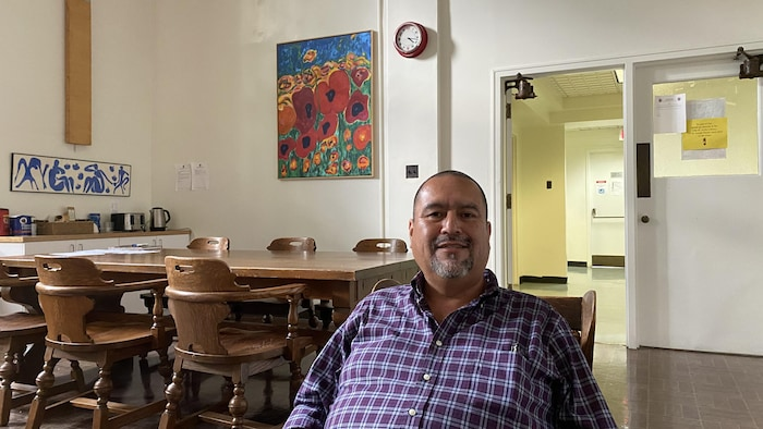 Portrait d'Oscar Vigil, directeur général du Conseil canadien du patrimoine hispanique, assis dans une classe. On voit des chaises et des tables derrière lui.