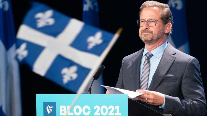 Yves-François Blanchet giving speech in front of microphone with Québec flags in background. Someone is also waving a Québec flag in front of camera.
