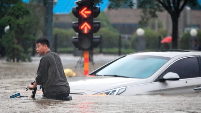 People walk, bike and try to make their way through flooded streets in Zhengzhou.