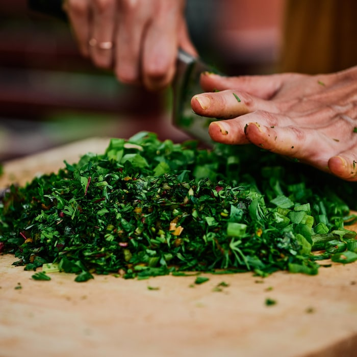 Plan rapproché sur des mains qui hachent des fanes de légumes.