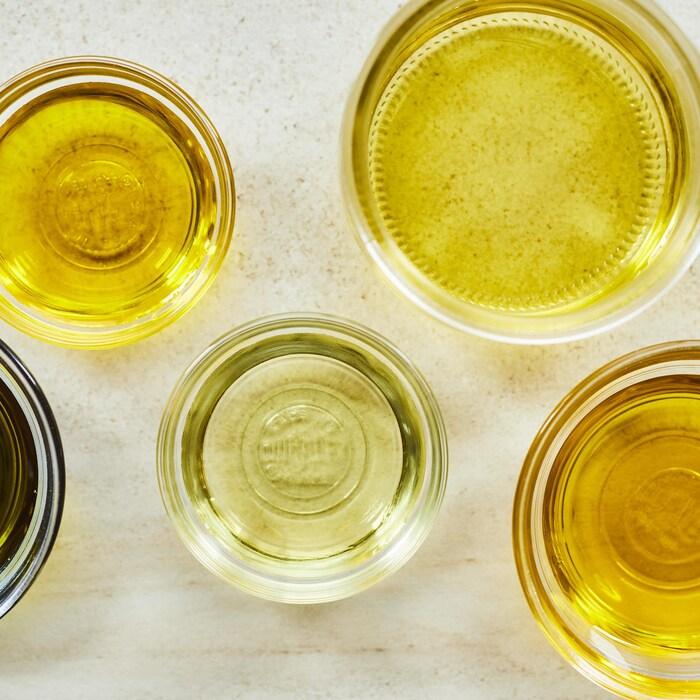 Différents types d'huiles dans des pots transparents.