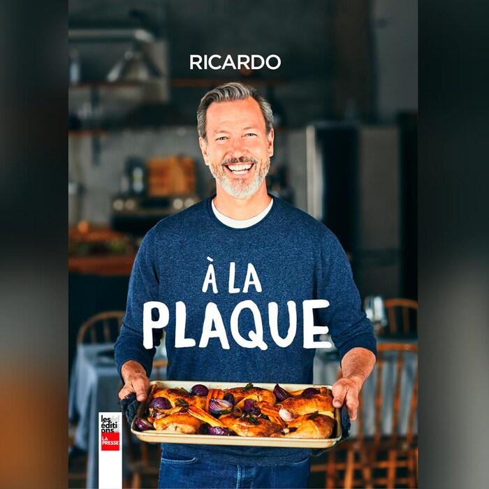 Ricardo sourit à la caméra avec dans les mains un plaque de poulet rôti avec des betteraves et des carottes.