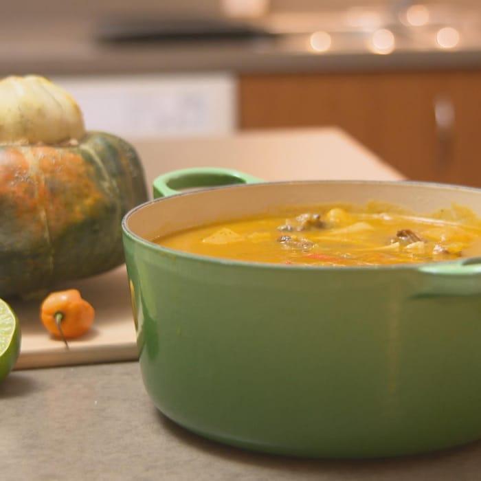 Un chaudron de soupe joumou et une courge giraumon sur un comptoir de cuisine.