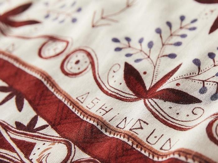 Un foulard avec un gros plan sur les motifs qui y figurent.