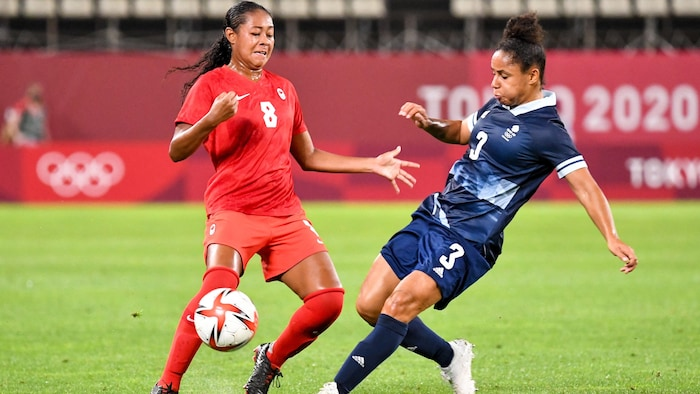 La defensora canadiense Jayde Riviere y la británica Demi Stokes luchan por el balón.