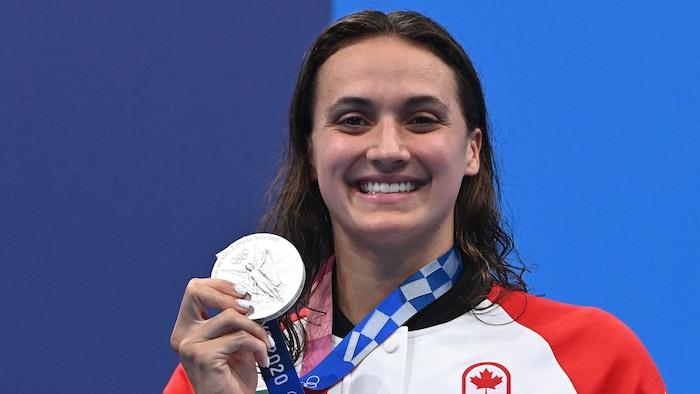 السبّاحة الكنديّة كايلي ماس ترفع ميداليّة برونزيّة.