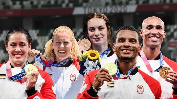 أبطال أولمبيون كنديّون يرفعون ميداليّاتهم.