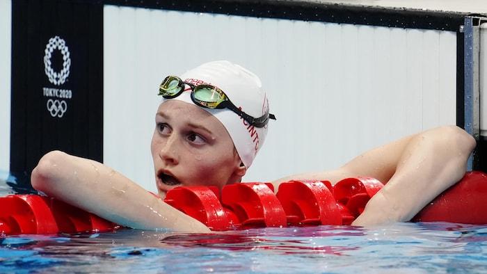 Un nadador descansa en las cuerdas mientras mira el tablero después de una prueba olímpica.