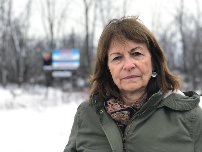 Janet Spring says even though her son-in-law has been found not guilty, her community is continuing to support Hondurans. Spring is standing in front on a billboard for Espinal by the side of a snowy road.