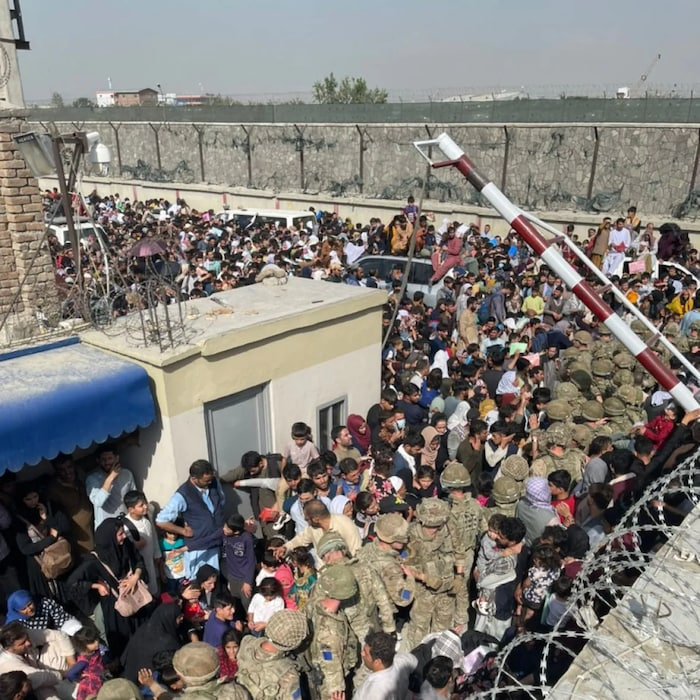 Hundreds of Afghan refugees crossing gate at Kabul Airport; soldiers in the middle of the crowd.