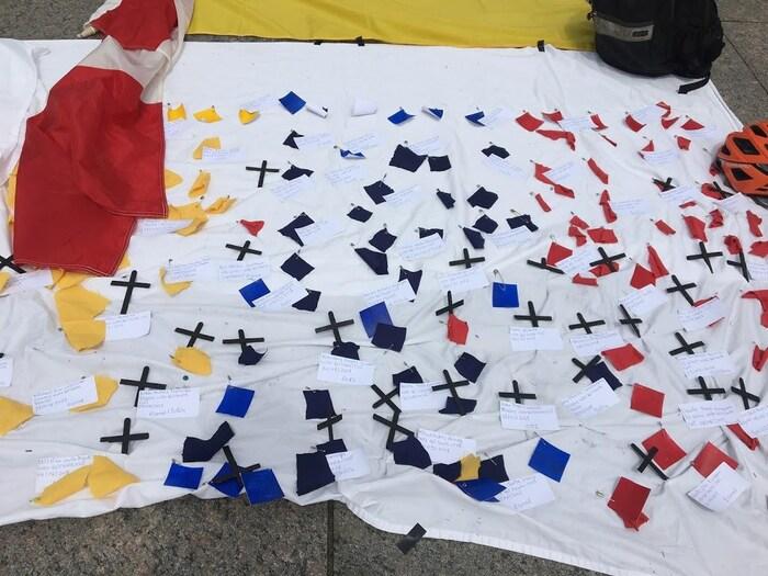 Una de las banderolas utilizadas por los organizadores del evento de Ottawa en donde se ven varias cruces con los nombres de algunas de las personas que han muerto durante las diversas manifestaciones civiles en el marco del Paro Nacional en Colombia.