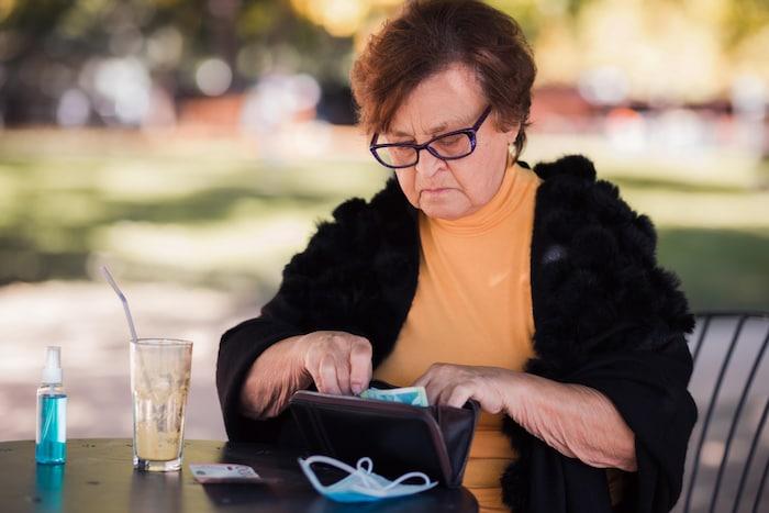 Una mujer buscando dinero en su cartera. El informe concluye que los ingresos medios de los ancianos indígenas y racializados son un 25% y un 32% inferiores, respectivamente, a los de los canadienses blancos.