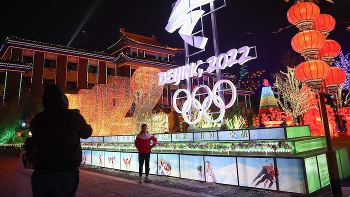 Une femme pose pour la caméra devant les anneaux olympiques.