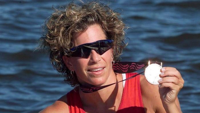 البطلة الأولمبيّة مارني ماكبين ترفع الميداليّة الذهبيّة.