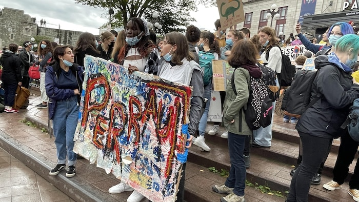Des élèves de l'école secondaire Joseph-François-Perrault avec leur pancarte.