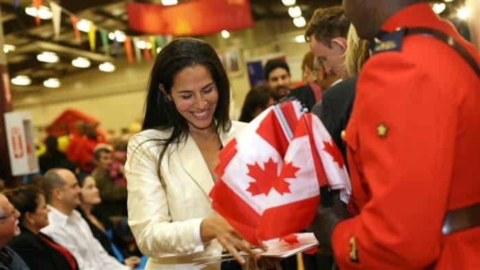 سيدة مهاجرة مسرورة بحصولها على الجنسية الكندية في حفل رسمي في هاليفاكس عاصمة مقاطعة نوفا سكوشا في شرق كندا، ونرى في الصورة أحد عناصر الشرطة الملكية الكندية بالزي الرسمي الأحمر حاملاً أعلاماً كندية.