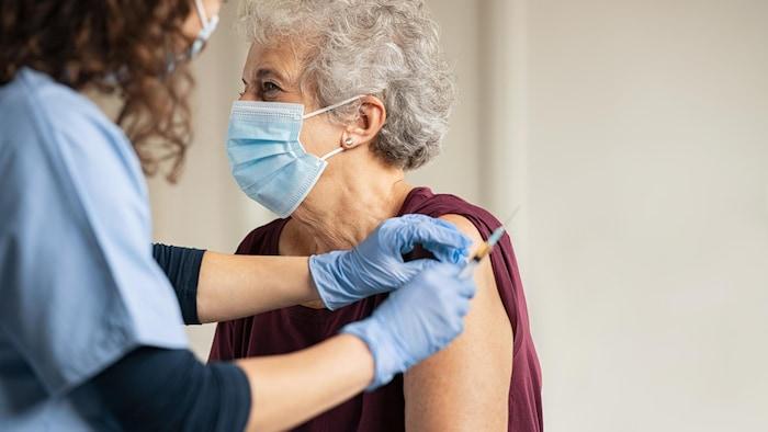 طبيبة تعطي لقاحاً مضاداً لوباء ''كوفيد - 19'' لامرأة مسنّة تضع غطاء وجه واقياً.