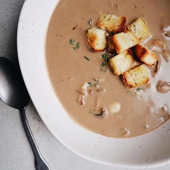 Photo d'une crème aux champignons servie dans une assiette avec des croûtons et du thym.