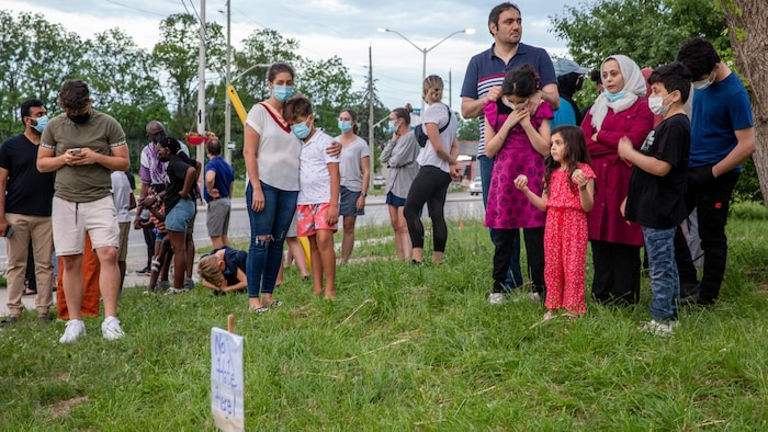 一些人在悼念遭到汽车有意撞击而丧生的穆斯林家庭。