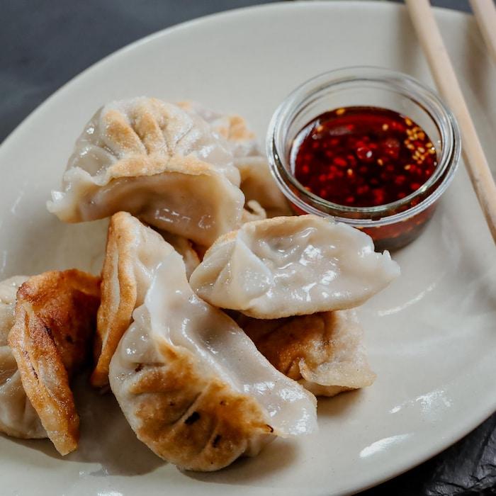 Une assiette remplie de dumplings au chou chinois et à la coriandre.