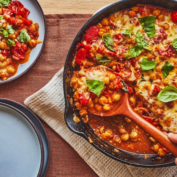 Poêlon en fonte plein de tomates, de pois chiches et de fromage.