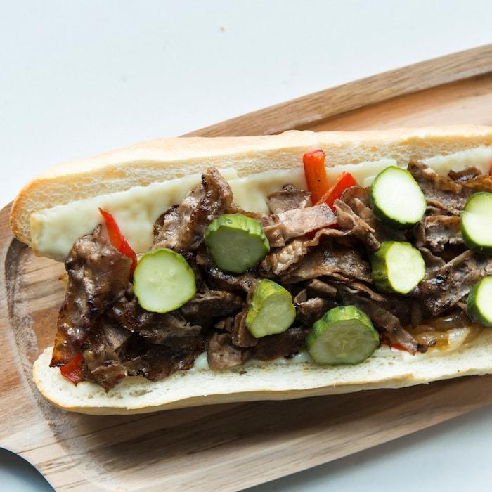 Un pain coupé en deux ouvert avec des tranches de bœuf, du fromage, des poivrons et des tranches de concombres marinés.