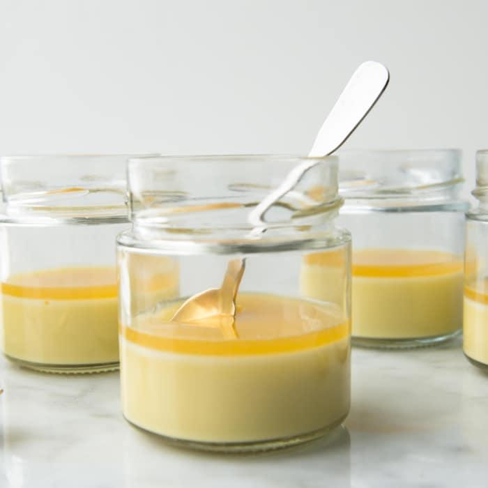 Cinq petits pots de crème en verre sont sur le comptoir.