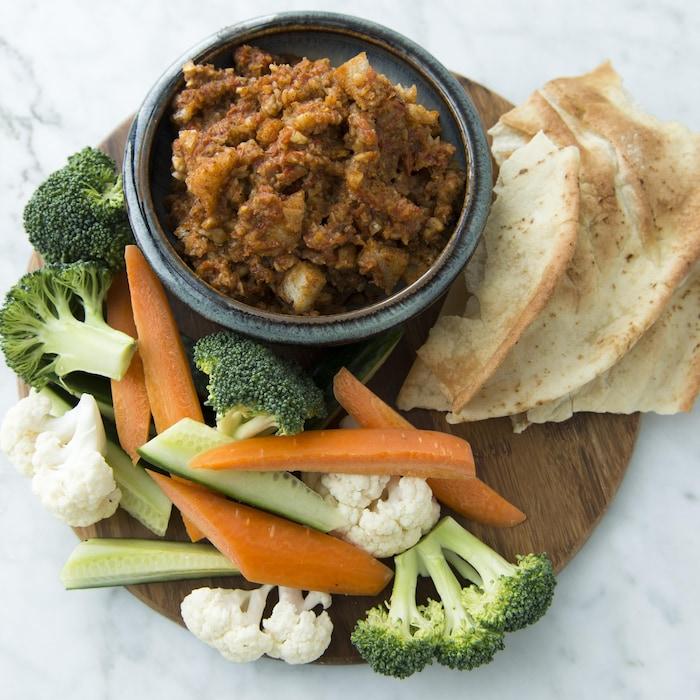 Le bol de sauce est sur une planche de bois avec ses accompagnements de pitas et de crudités.