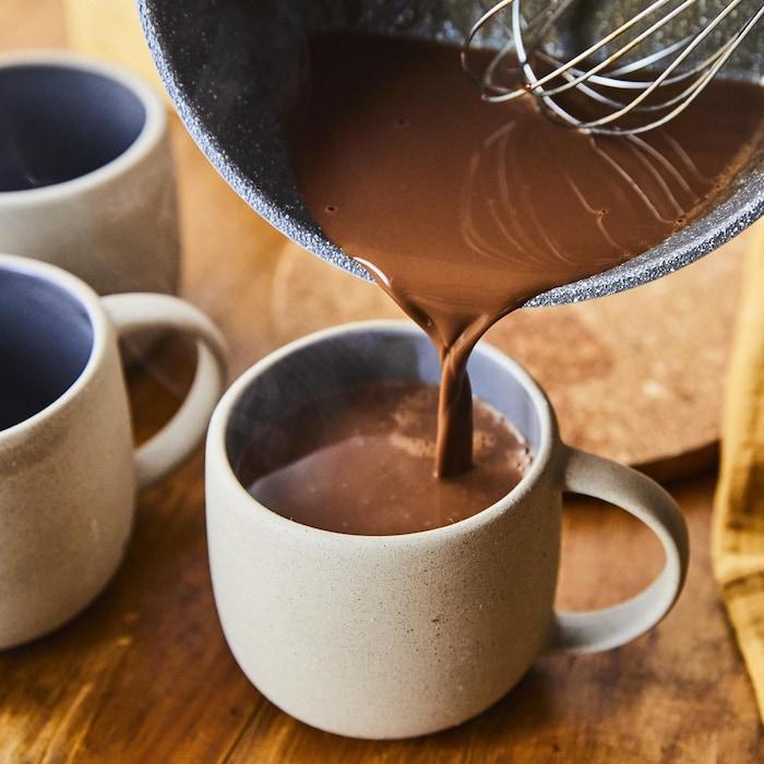 On verse le chocolat chaud dans une tasse.