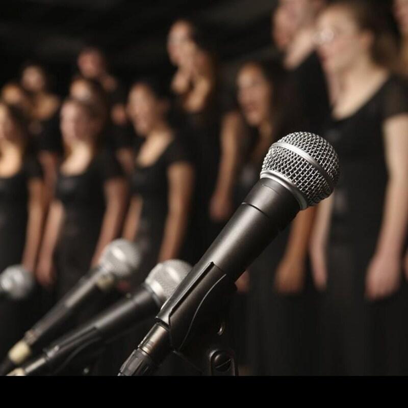 Image floue d'une chorale avec au premier plan des micros.