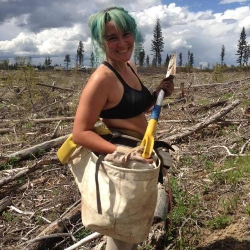 une femme porte un sac plein de graines pour reforester une prairie.