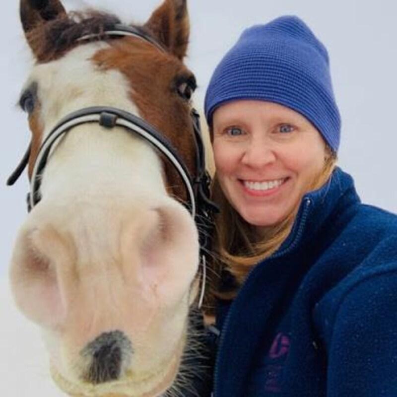 Une femme sourit à côté d'un cheval.