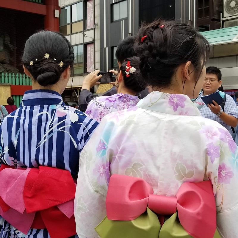 Deux femmes habillées en costume traditionnel sont montrées de dos.