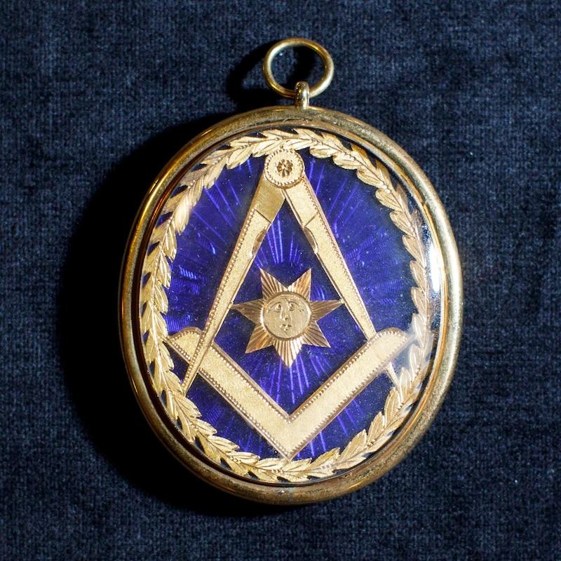 Un médaillon maçonnique gravé des symboles de l'équerre et du compas.