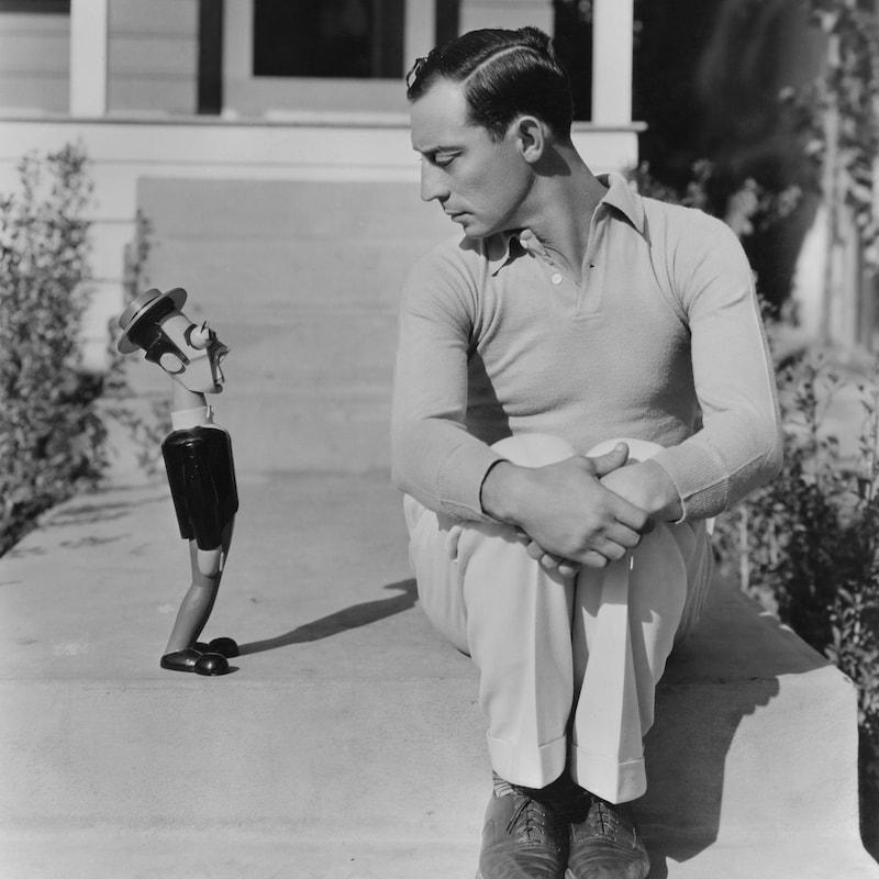 Assis, Buster Keaton regarde une poupée se trouvant à côté de lui.