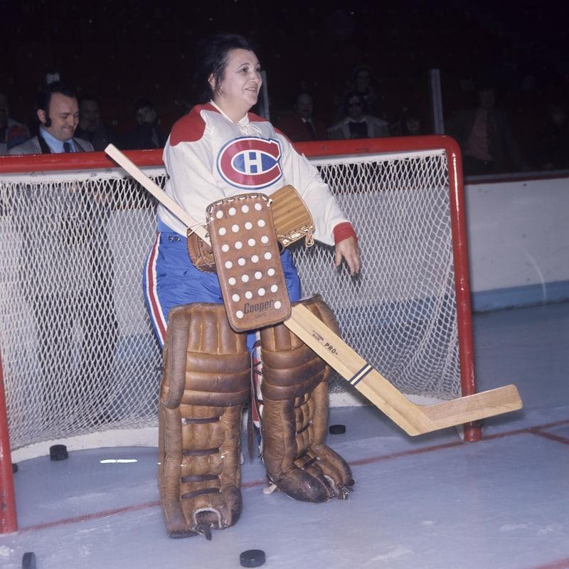 Lise Payette en habit de hockey du Canadien, devant un filet sur la patinoire du Forum de Montréal.
