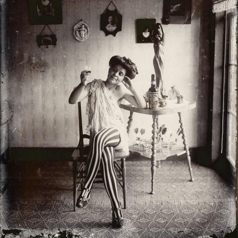 Une femme légèrement vêtue, assise sur une chaise et accoudée contre une table, lève un petit verre.
